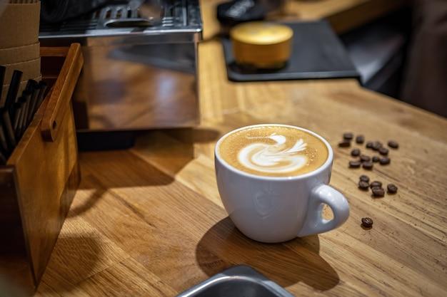 Cappuccinokaffee mit abstraktem muster in einem weinlesecafé.