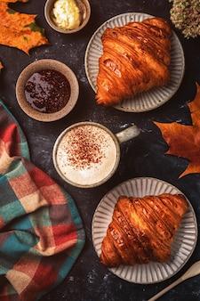 Cappuccinokaffee mit hörnchen auf dem tisch, herbstfrühstückskonzept, draufsicht