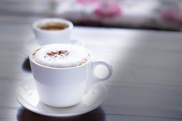 Cappuccinokaffee mit kakao belegt in der weißen schale im café mit morgentageslicht.