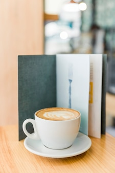 Cappuccinokaffee mit kunst latte und menü auf holztisch