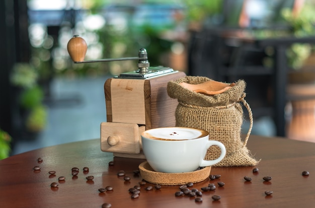 Cappuccinokaffeetasse auf hölzerner tabelle mit traditionellen kaffeebohnen und schleifer