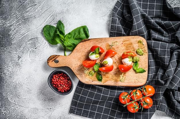 Caprese-salat am spieß, tomate, pesto und mozzarella. canapes snack