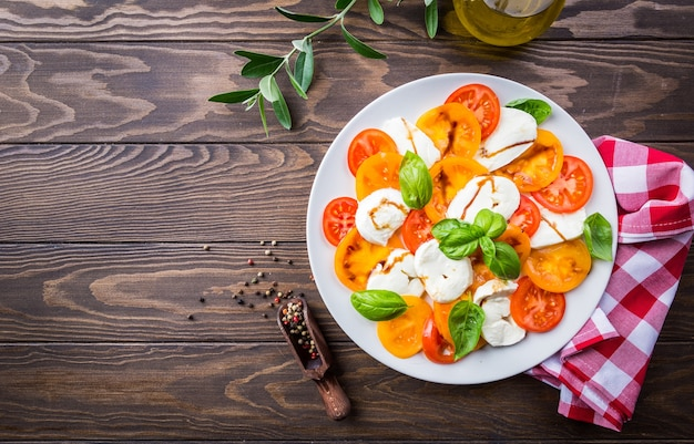 Caprese-salat aus mozzarella-käse, gelben tomaten und basilikumblättern auf holz. draufsicht.