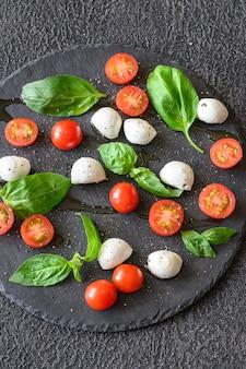 Caprese-salat aus mozzarella, tomaten und süßem basilikum