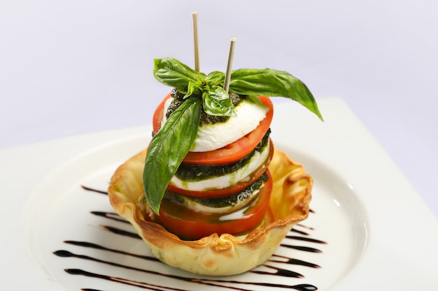 Caprese-salat, italienischer salat. tomatenscheiben, frischer mozzarella und basilikumblätter mit olivenöl.