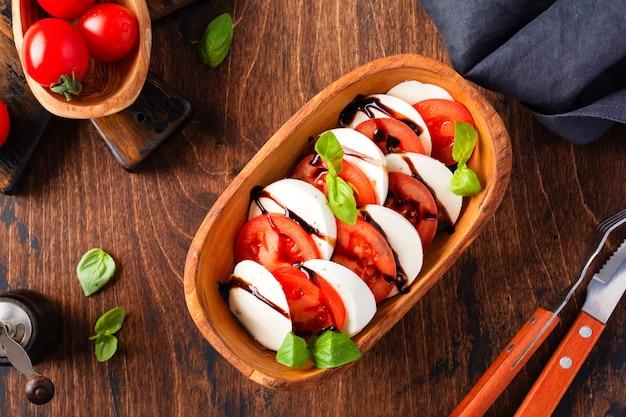 Caprese-salat italienisches essen mit reifen tomaten, frischem gartenbasilikum und mozzarella-käse in olivenholzschale auf altem rustikalem hintergrund. draufsicht flach legen
