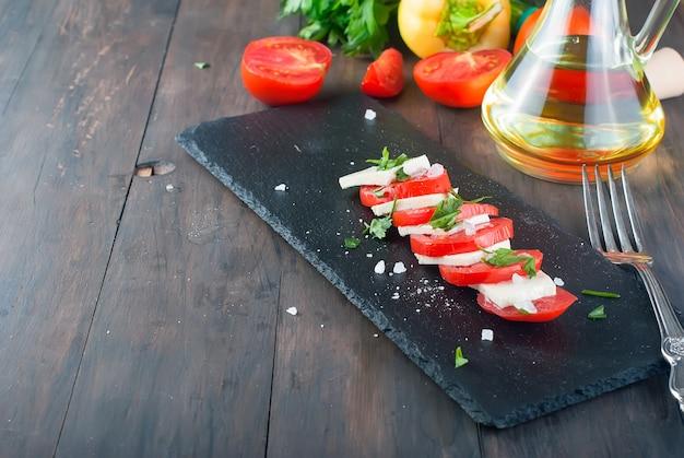 Caprese-salat mit frischkäse und tomaten.