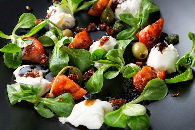 Caprese-salat mit mozzarella, tomate, basilikum und balsamico-essig auf schwarzem teller angeordnet