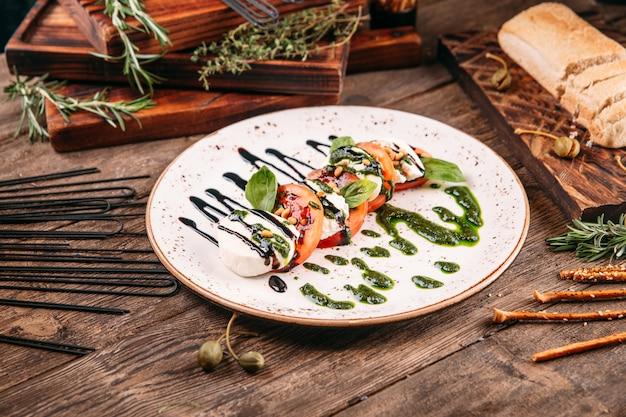 Caprese-salat mit pesto-sauce auf dem holztisch