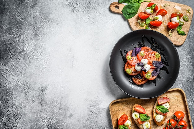 Caprese-salat, spieß-häppchen und bruschettes mit kirschtomaten, mozzarella und basilikum. draufsicht. speicherplatz kopieren