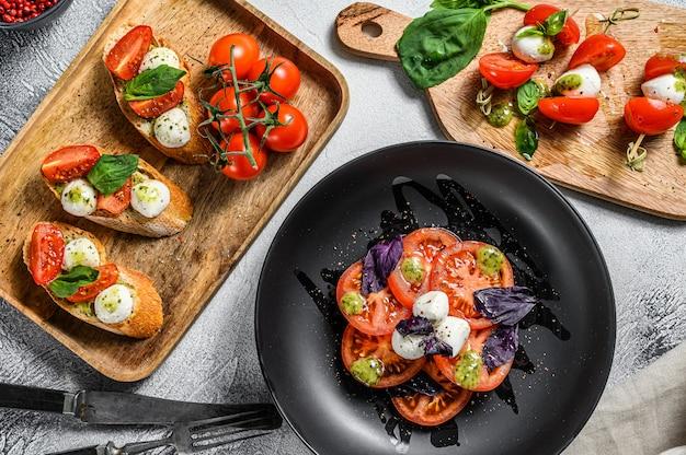 Caprese-salat, spieß-häppchen und bruschettes mit kirschtomaten, mozzarella und basilikum. grauer hintergrund. draufsicht
