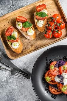 Caprese-salat, spieß-häppchen und bruschettes mit kirschtomaten, mozzarella und basilikum