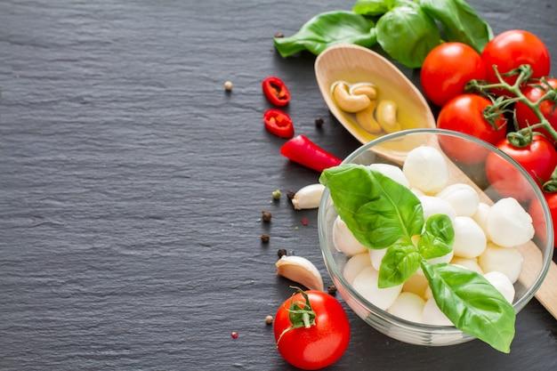 Caprese-salatbestandteile auf dunklem steinhintergrund