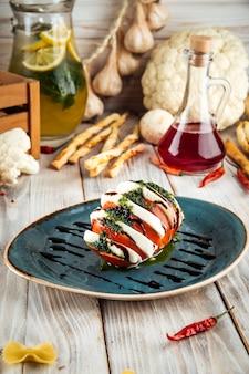 Caprese salattomate und mozzarella in pesto-sauce