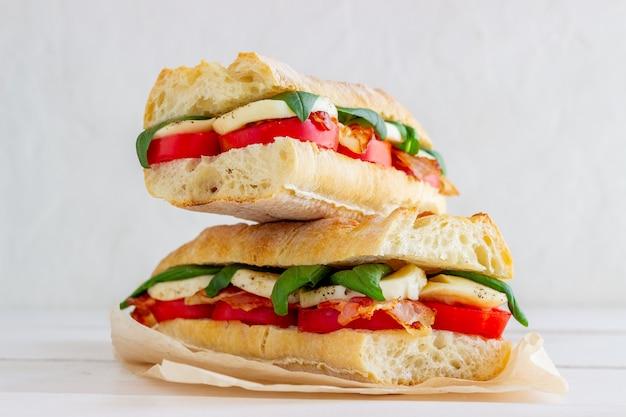 Caprese-sandwich mit tomaten, mozzarella, basilikum und speck. gesundes essen. italienische küche.