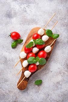 Caprese-spieße mit mozzarella, tomaten und basilikum