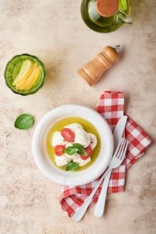 Capresesalat. mozzarella-käse mit basilikum und kirschtomate in weißer keramikplatte und tomatenkirsche auf schiefersteintischhintergrund, kopierraum. attrappe, lehrmodell, simulation.