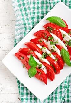 Capresesalat. tomaten- und mozzarella-scheiben mit basilikumblättern.