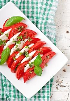 Capresesalat. tomaten- und mozzarellascheiben mit basilikumblättern.