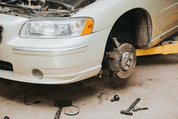 Car service center konzept, fahrzeug am lift an der wartungsstation angehoben, autoreparatur und kontrolle, reparatur des autos