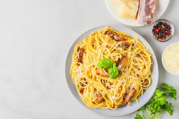 Carbonara pasta, spaghetti mit speck, ei, hartparmesan und basilikum in einem teller. traditionelle italienische küche