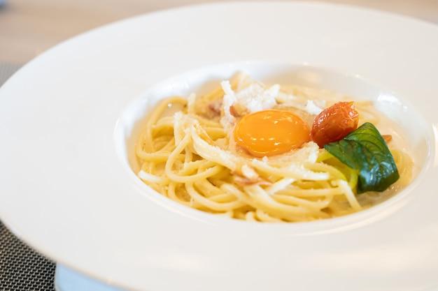 Carbonara-saugeteigwaren mit rohem ei auf der weißen platte