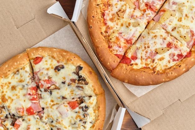 Carbonara und hawaii-pizza in einem karton mit einer draufsicht