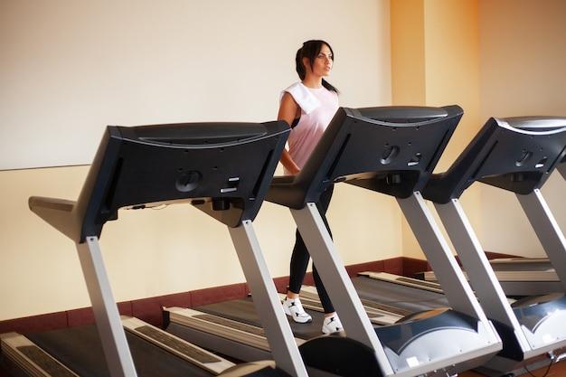 Cardio-training. geeignete frauen, die auf den tretmühlen tun herz training in einer turnhalle, gesundes lebensstilkonzept laufen