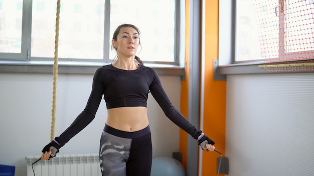Cardio-training mit dem fitnessstudio. junge frau seilspringen
