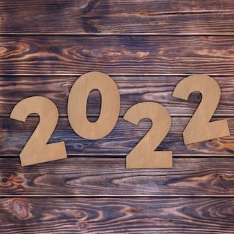 Cardstock numbers 2022 frohes neues jahr schild über holztisch hintergrund. 3d-rendering