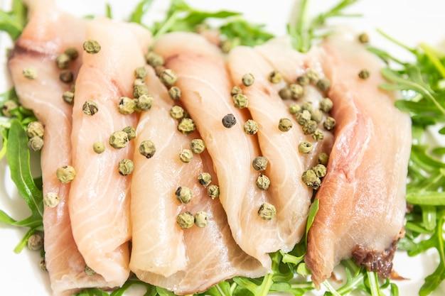 Carpaccio aus frischem mediterranem schwertfisch mit grünem pfeffer, schnittlauch und einigen tropfen orangensaft