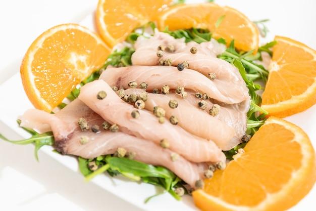 Carpaccio aus frischem mediterranen schwertfisch mit grünem pfeffer, schnittlauch und ein paar tropfen orangensaft