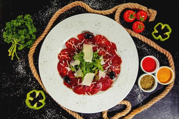 Carpaccio vom rind mit parmesan, rucola und oliven