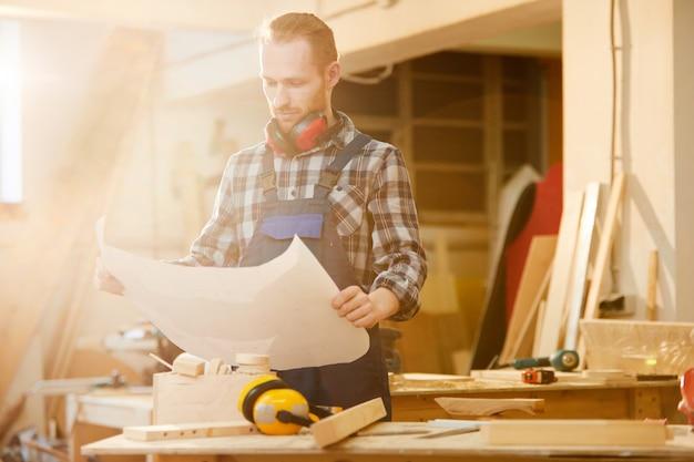Carpenter holding pläne