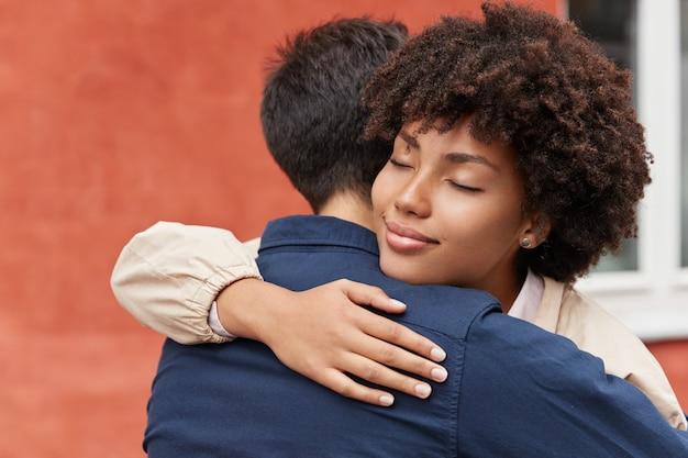 Carying frau umarmt ihren freund, hat gesichtsausdruck erfreut