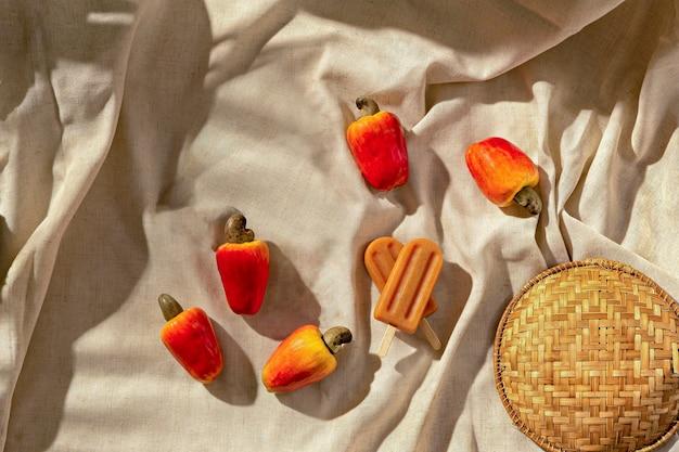 Cashew-eis am stiel mit cachew-früchten auf stoffunterlage, sonnenlicht, draufsicht