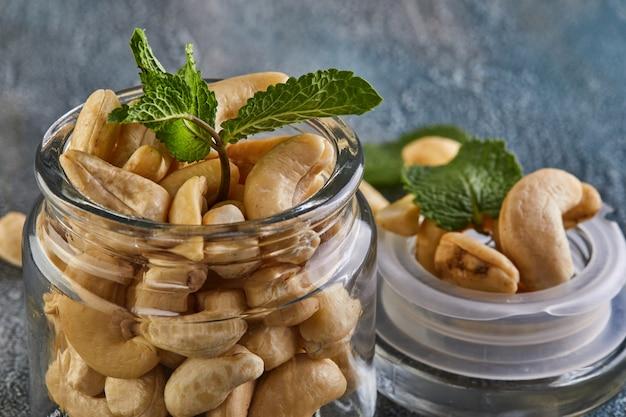 Cashew in einem durchsichtigen glas mit minzblättern darauf