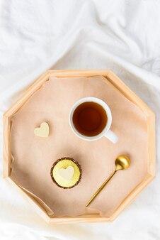 Cashewkuchen mit einer tasse tee auf einem tablett auf dem bett.
