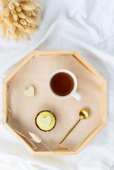 Cashewkuchen mit einer tasse tee auf einem tablett mit getrockneten blumen auf dem bett