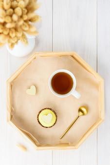 Cashewkuchen mit einer tasse tee auf einem tablett mit getrockneten blumen
