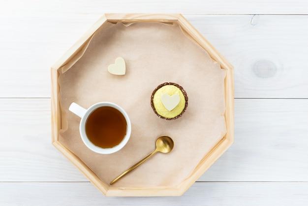 Cashewkuchen mit schokoladenherz und einer tasse tee auf einem holztablett