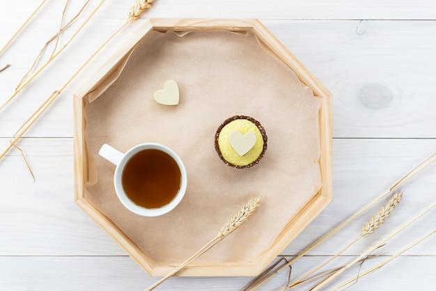 Cashewkuchen mit weißem schokoladenherz und einer tasse tee auf einem holztablett