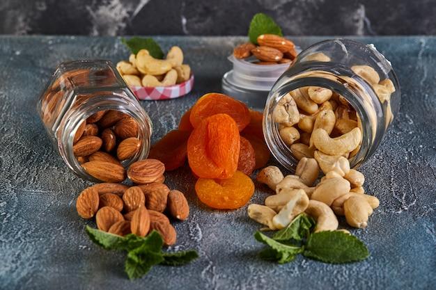 Cashewmandeln quellen aus durchsichtigen dosen, dazwischen liegen getrocknete aprikosen