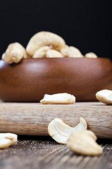 Cashewnüsse auf einem alten holztisch und in einer holzschale, nahaufnahme einer großen anzahl von cashewnüssen auf einem tisch und auf einer holzoberfläche in einer holzplatte