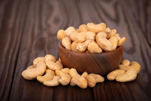 Cashewnüsse holzschale, auf hölzernem hintergrund. geröstete cashewnüsse.