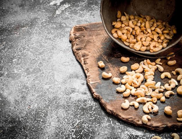 Cashewnüsse im alten eimer. auf rustikalem hintergrund.