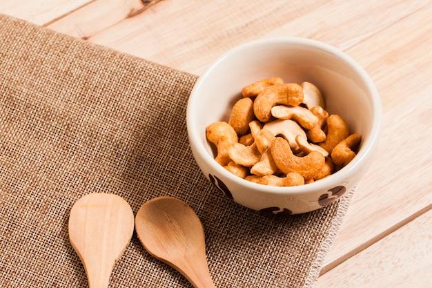 Cashewnüsse in der schüssel setzen auf sack und holztisch und holzlöffel.