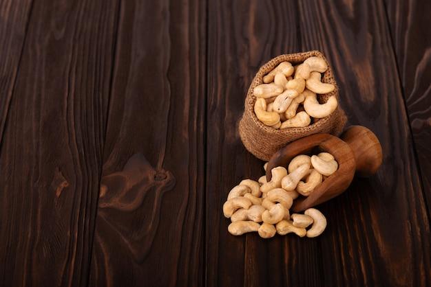 Cashewnüsse in der tasche und in der hölzernen schaufel, auf hölzernem hintergrund. geröstete cashewnüsse.
