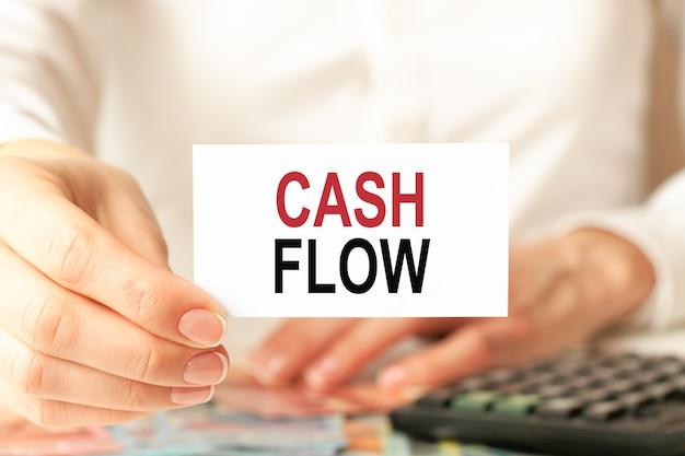 Cashflow wird auf eine weiße visitenkarte geschrieben. die hand einer frau hält eine weiße papierkarte, weißer hintergrund. geschäfts- und werbekonzept. defokussieren.