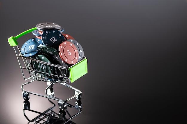 Casino-chips in einem einkaufskorb auf einem dunklen hintergrund mit reflexion